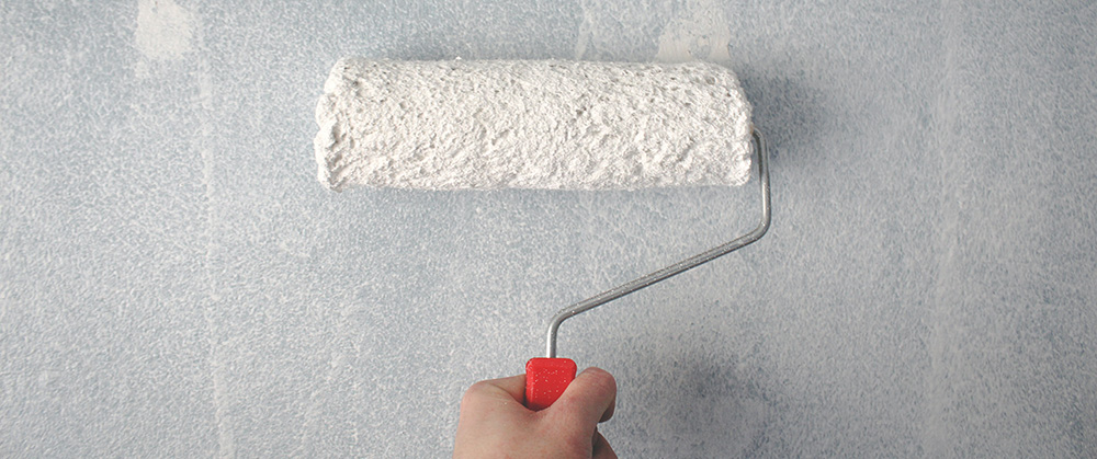 Wet Paint Brush Painting a Wall